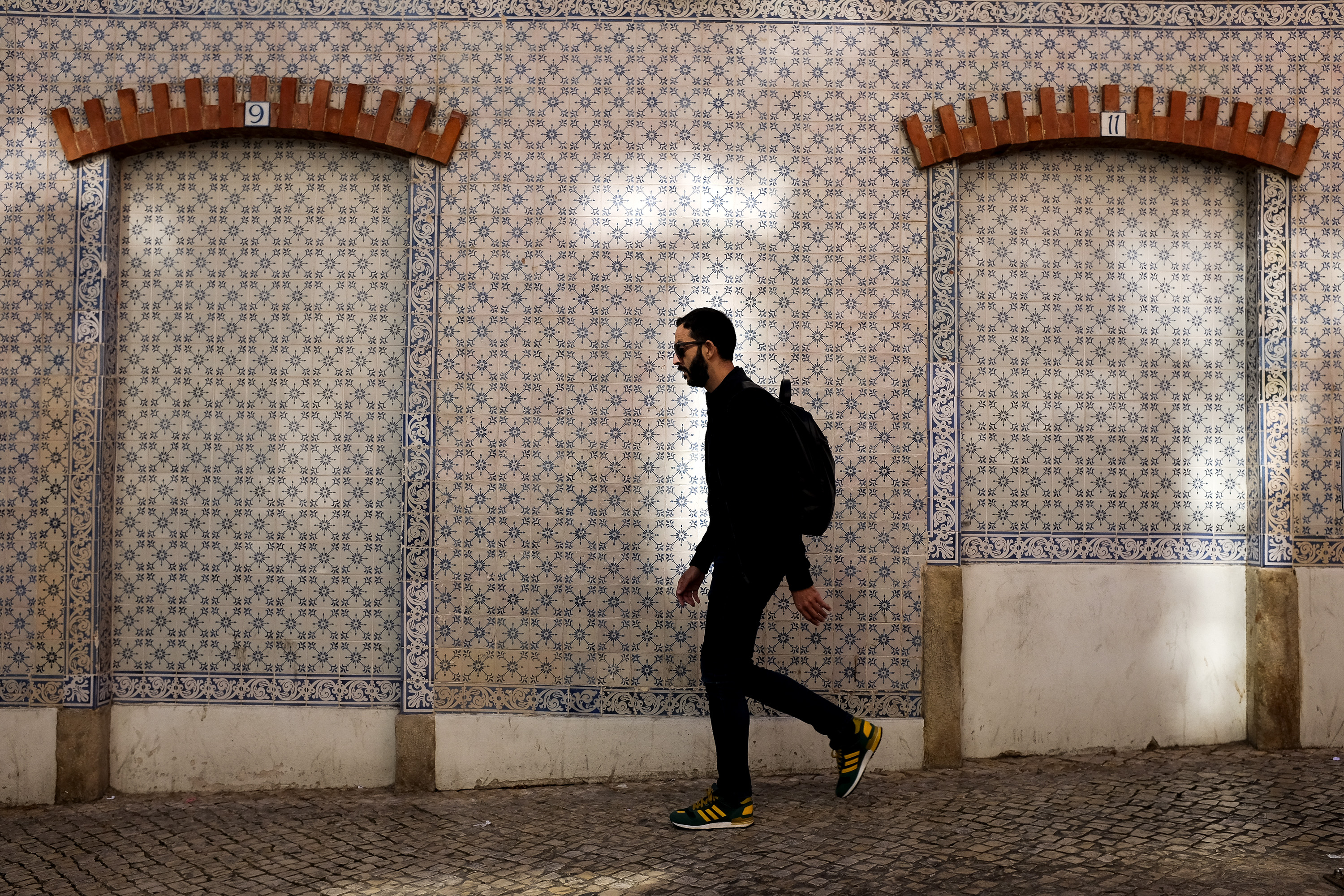 A random person walking downwards with a building frontage covered in tiles in the background